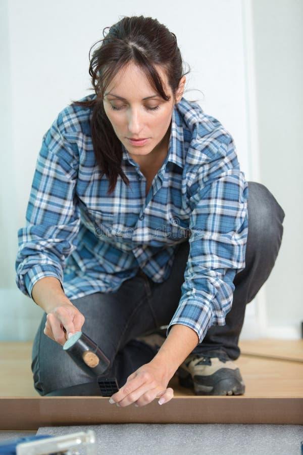 Mulher que coloca o revestimento de madeira do painel na casa foto de stock