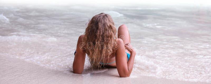 Mulher que coloca pelo mar tropical imagens de stock royalty free