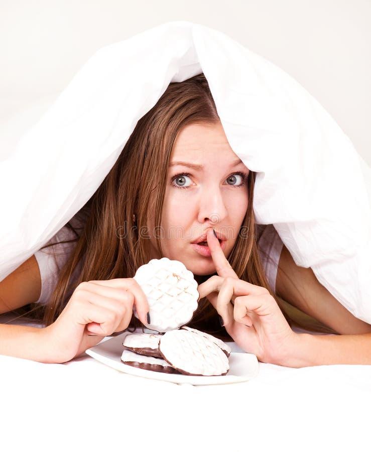 Mulher que come bolinhos imagem de stock