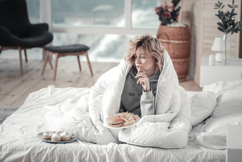Mulher que come a comida lixo em sua cama após a dissolução com noivo foto de stock royalty free