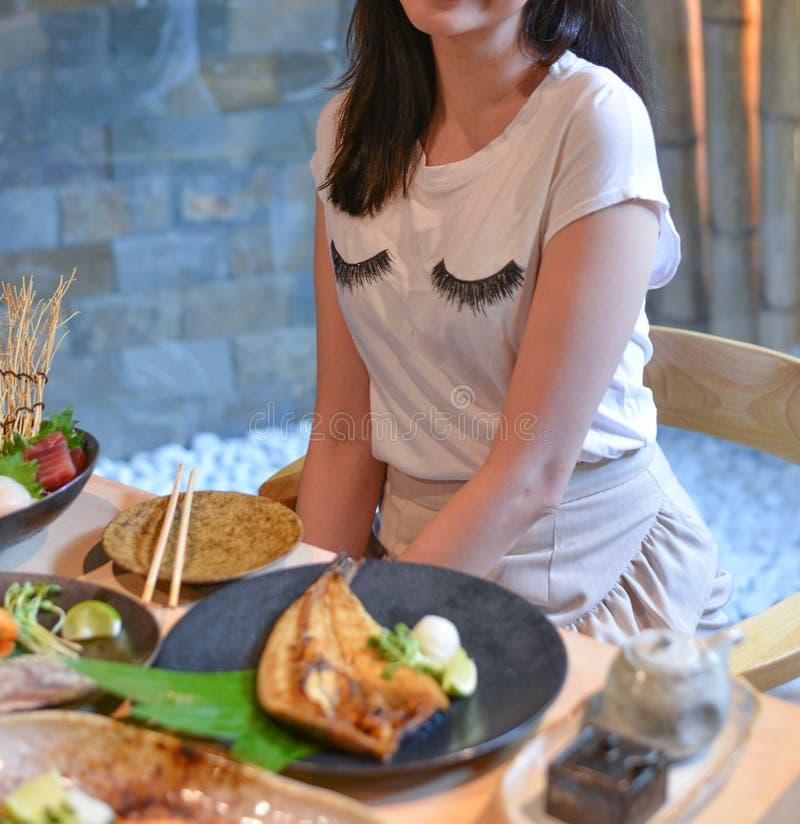 Mulher que come e que aprecia a refeição japonesa foto de stock