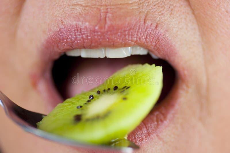Mulher que come a fruta de quivi foto de stock