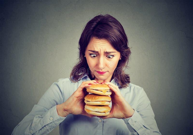 Mulher que come implorando um hamburguer triplo saboroso imagem de stock royalty free