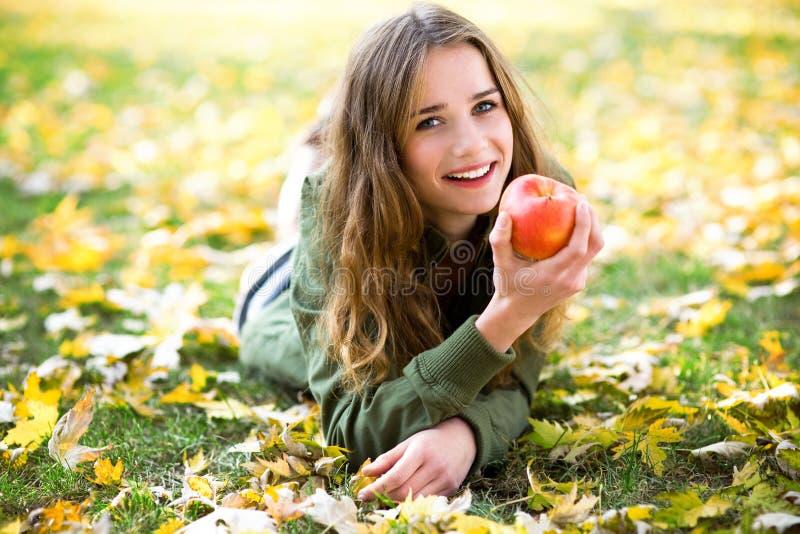 Mulher que come a maçã ao ar livre no outono imagens de stock