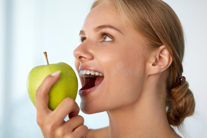 Mulher que come a maçã Menina bonita com dentes brancos que morde Apple fotografia de stock royalty free