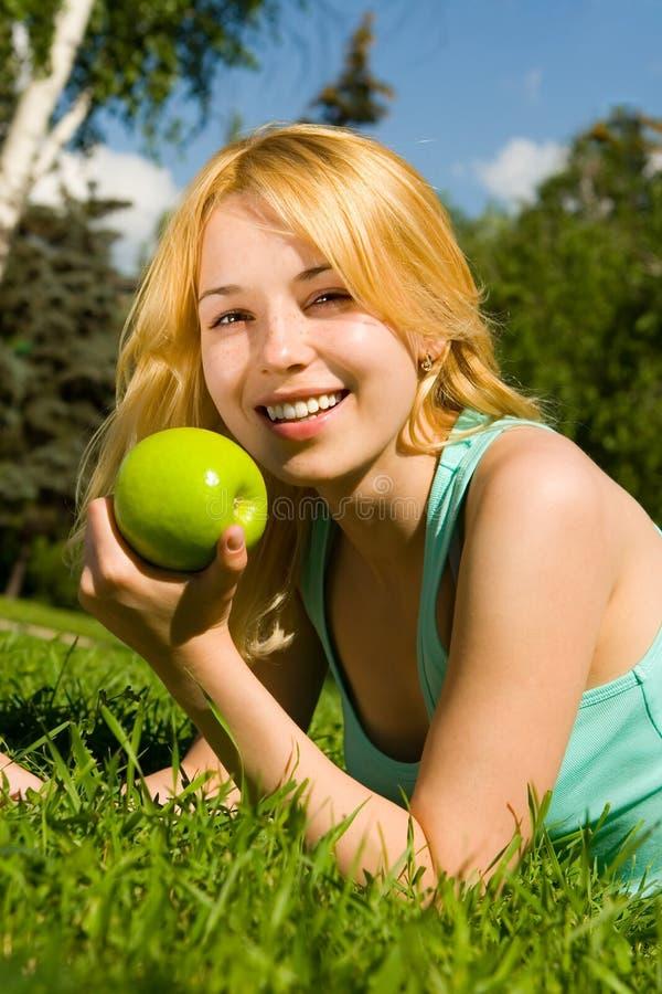 Mulher que come a maçã verde no glade do verão fotos de stock royalty free