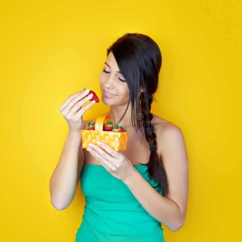 Mulher que come morangos foto de stock royalty free