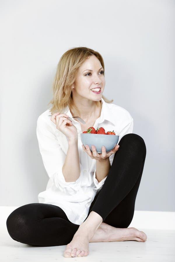 Mulher que come morangos frescas fotos de stock