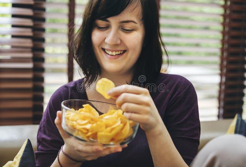 Mulher que come o alimento insalubre apenas imagens de stock