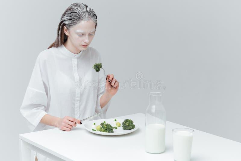 Mulher que come o alimento saudável na tabela imagem de stock