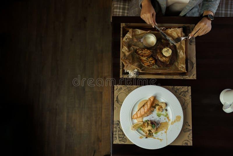 Mulher que come o bife da carne com vegetais cozidos em um restaurante Almoço saudável e saboroso Vista superior da mesa de janta imagem de stock