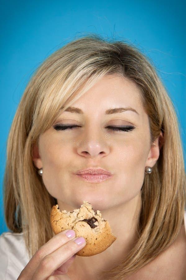 Mulher que come o bolinho fotografia de stock royalty free
