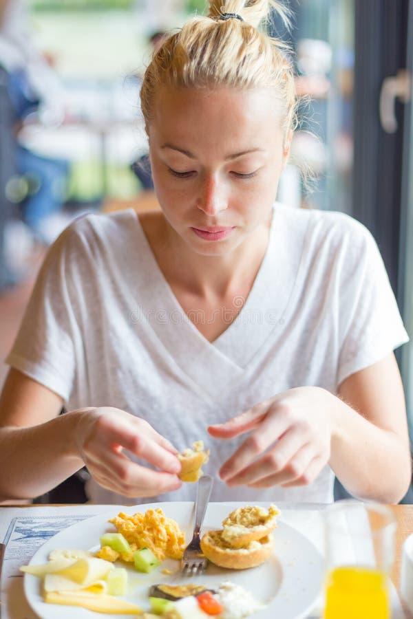 Mulher que come o café da manhã saudável delicioso: ovos mexidos, queijo, vegetais, pão e suco de laranja fotografia de stock royalty free