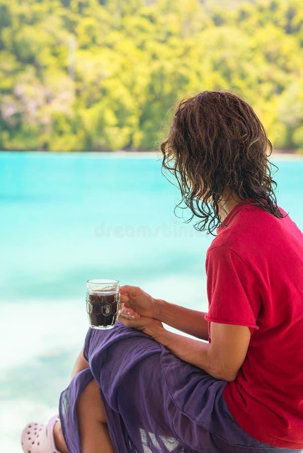 Mulher que come o café na lagoa azul imagens de stock royalty free