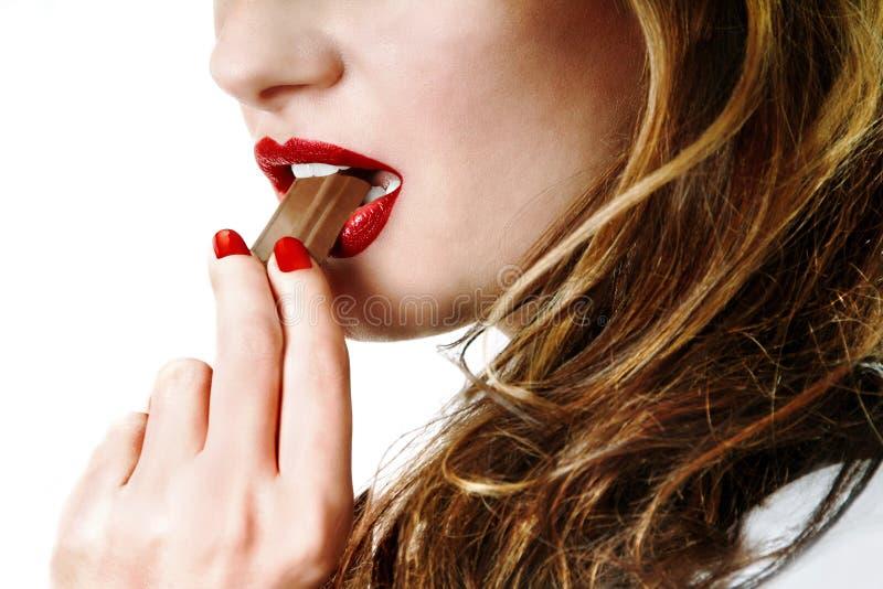 Mulher que come o chocolate de leite imagem de stock