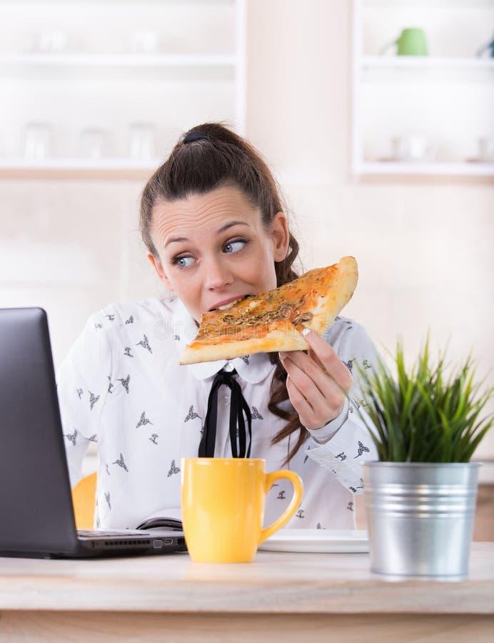 Mulher que come o fast food e que trabalha no portátil fotos de stock