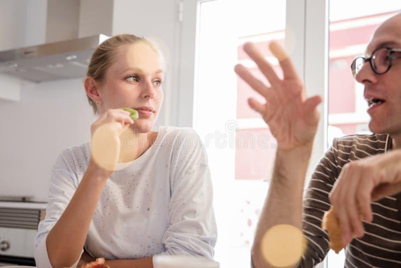 Mulher que come o fruto de quivi em uma tabela em uma cozinha foto de stock royalty free