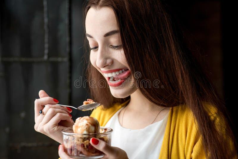 Mulher que come o gelado no café imagens de stock royalty free