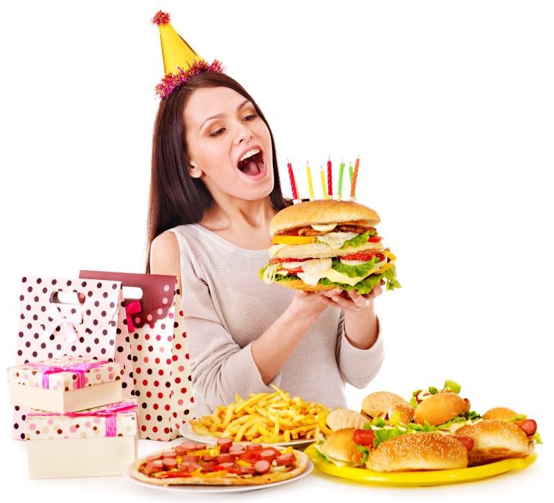 Mulher que come o Hamburger no aniversário. fotografia de stock royalty free