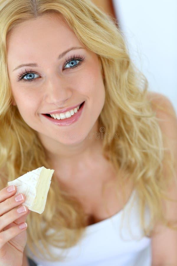 Mulher que come o queijo foto de stock