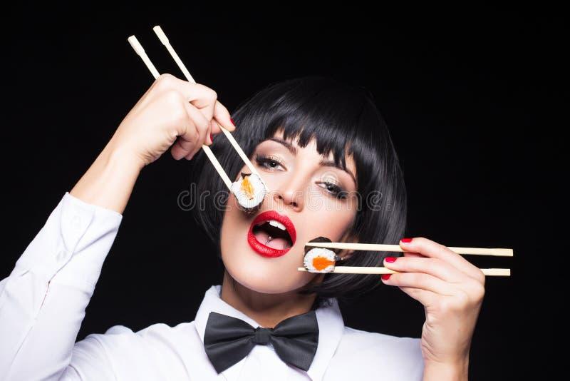 Mulher que come o sushi por dois hashis fotos de stock