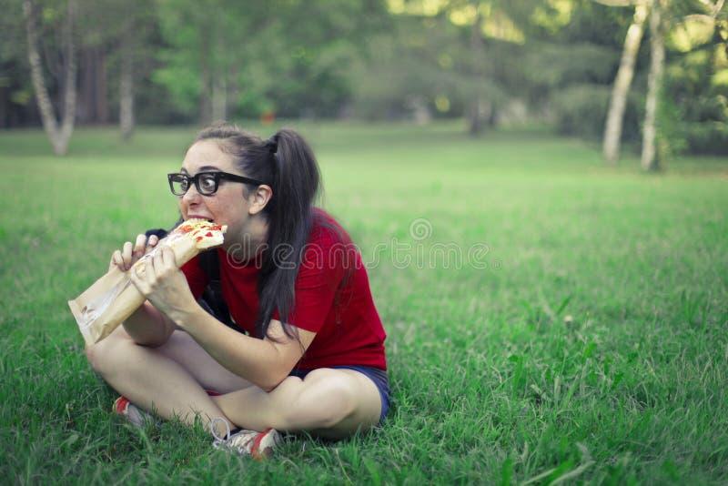 Mulher que come a pizza imagens de stock