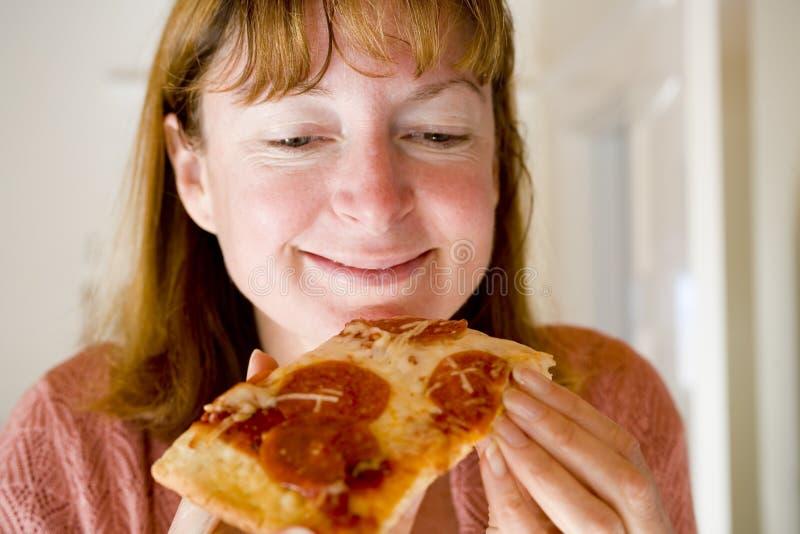 Mulher que come a pizza de Pepperoni fotos de stock royalty free