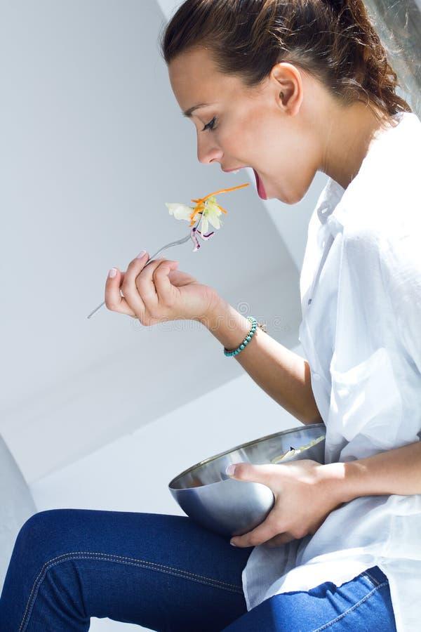 Mulher que come a salada em casa