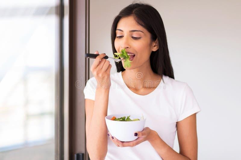 Mulher que come a salada verde imagem de stock