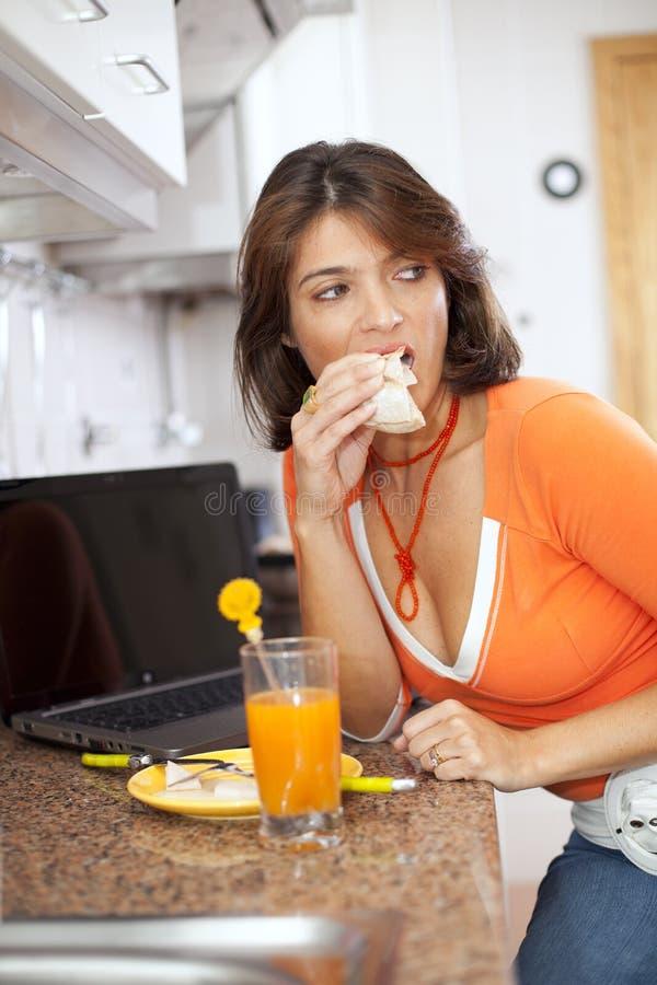 Mulher que come seu pequeno almoço imagens de stock royalty free