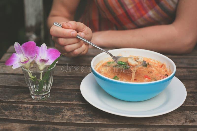 Mulher que come a sopa de tom yum fotografia de stock