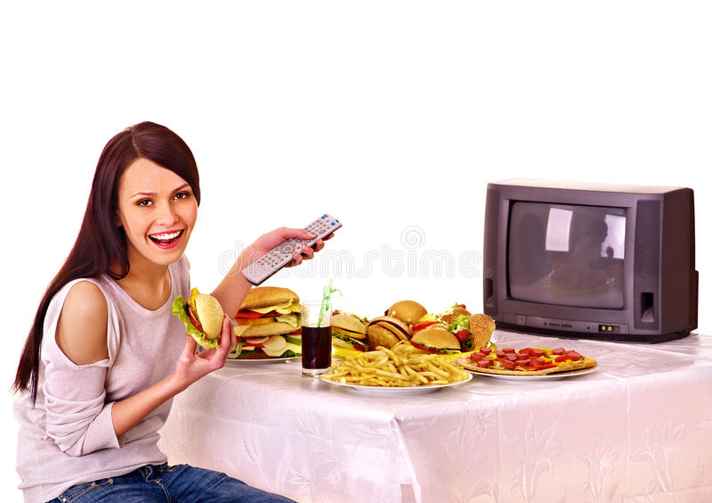 Mulher que come a tevê do fast food e da observação. imagens de stock royalty free