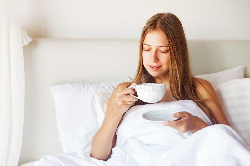 Mulher que come um café em uma cama fotografia de stock