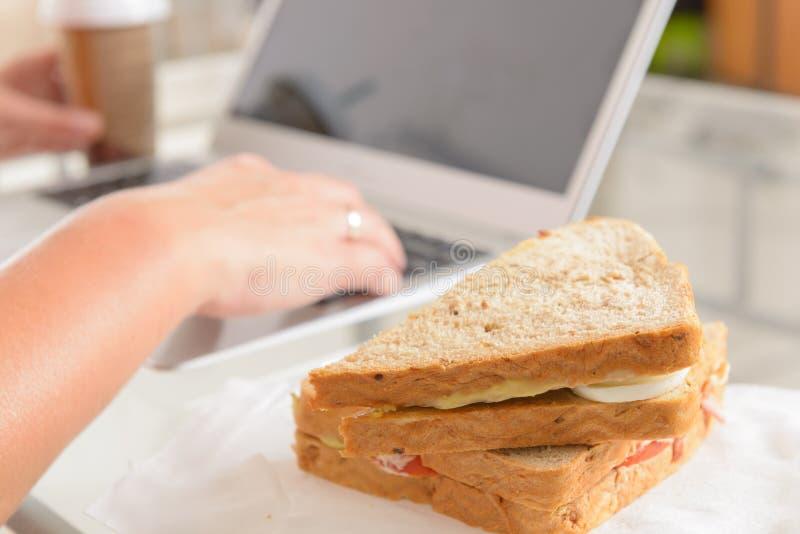 Mulher que come um sanduíche do café da manhã ao trabalhar com um portátil fotos de stock