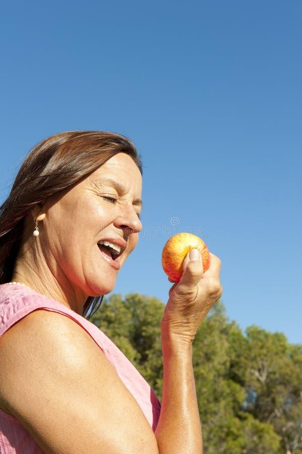 Mulher que come uma maçã fotografia de stock