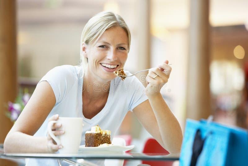 Mulher que come uma parte de bolo na alameda imagem de stock