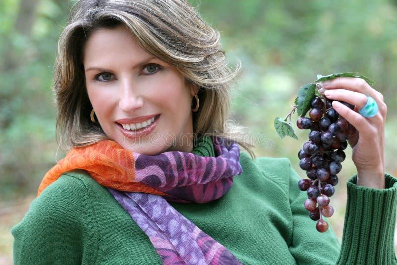 Mulher que come uvas, tema da queda imagens de stock