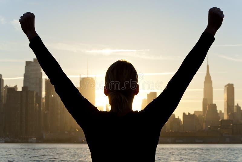 Mulher que comemora no nascer do sol em New York City fotos de stock