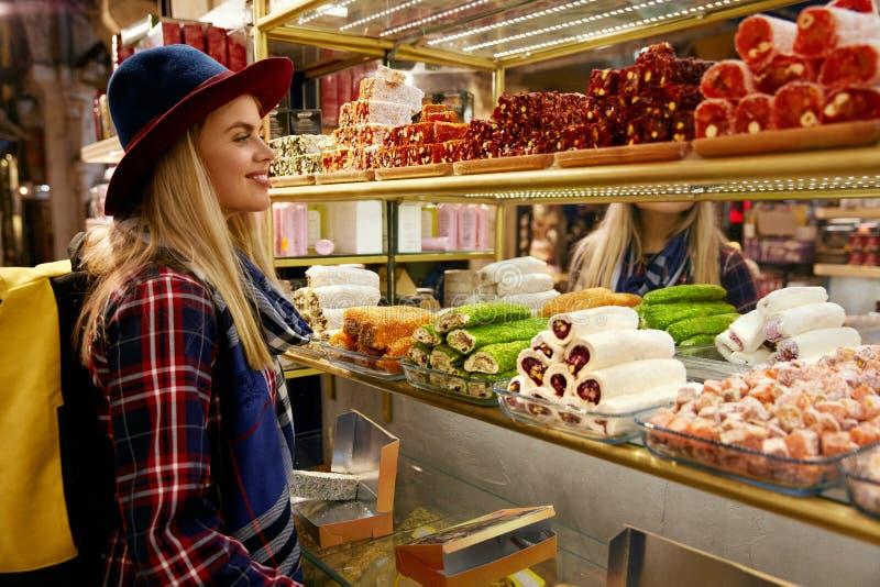 Mulher que compra doces turcos no mercado oriental do alimento fotografia de stock royalty free