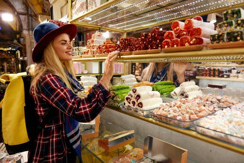 Mulher que compra doces turcos no mercado oriental do alimento foto de stock