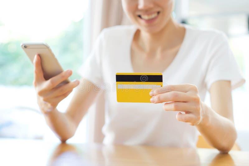 Mulher que compra em linha com um telefone esperto fotografia de stock royalty free