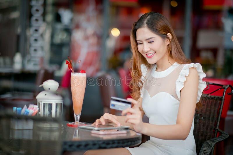 Mulher que compra em linha em férias com um portátil fotos de stock