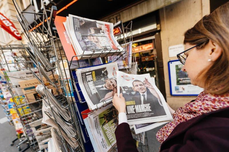 Mulher que compra a imprensa internacional com Emmanuel Macron Liberation imagem de stock
