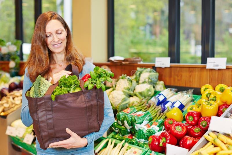 Mulher que compra legumes frescos na loja de alimento biológico imagem de stock