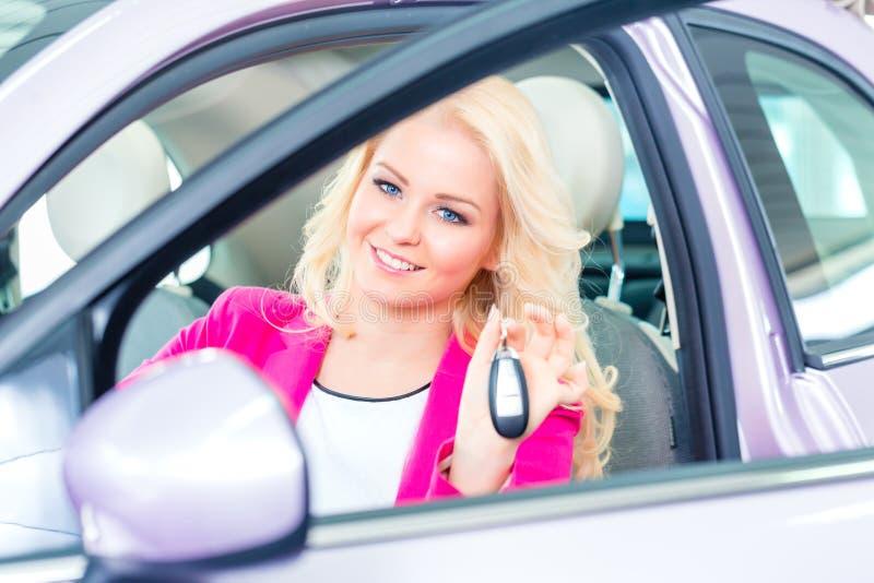 Mulher que compra o carro novo no negócio imagens de stock