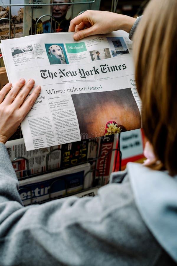 Mulher que compra o jornal de New York Times fotografia de stock royalty free
