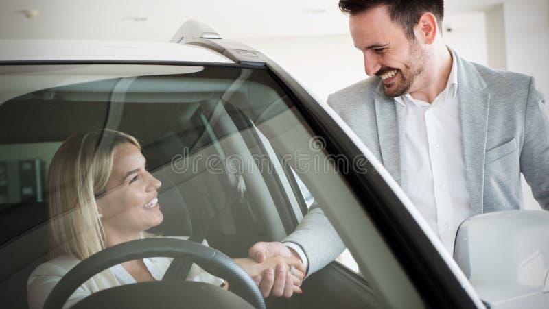 Mulher que compra um carro no negócio que senta-se em seu automóvel novo foto de stock royalty free