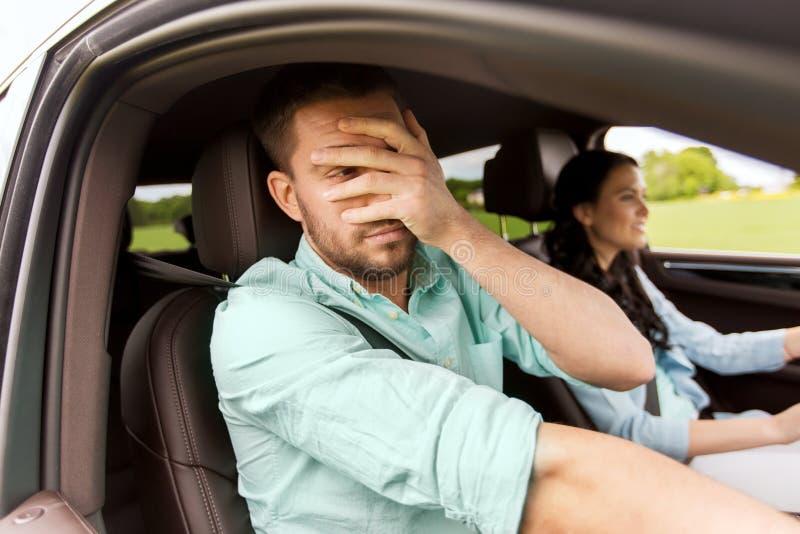 Mulher que conduz a cara da coberta do carro e do homem com palma imagens de stock royalty free