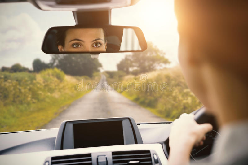 Mulher que conduz com sua reflexão no espelho fotos de stock