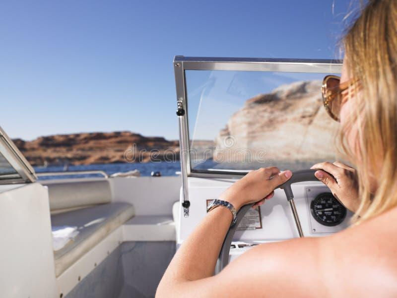 Mulher que conduz o barco fotos de stock
